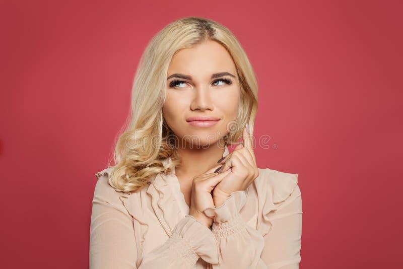Jonge gelukkige vrouw op roze achtergrond, grappig gezicht royalty-vrije stock fotografie