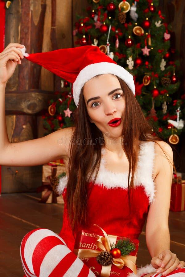 Jonge gelukkige vrouw in rode santahoed en rode kleding dichtbij nieuw jaar t royalty-vrije stock afbeelding
