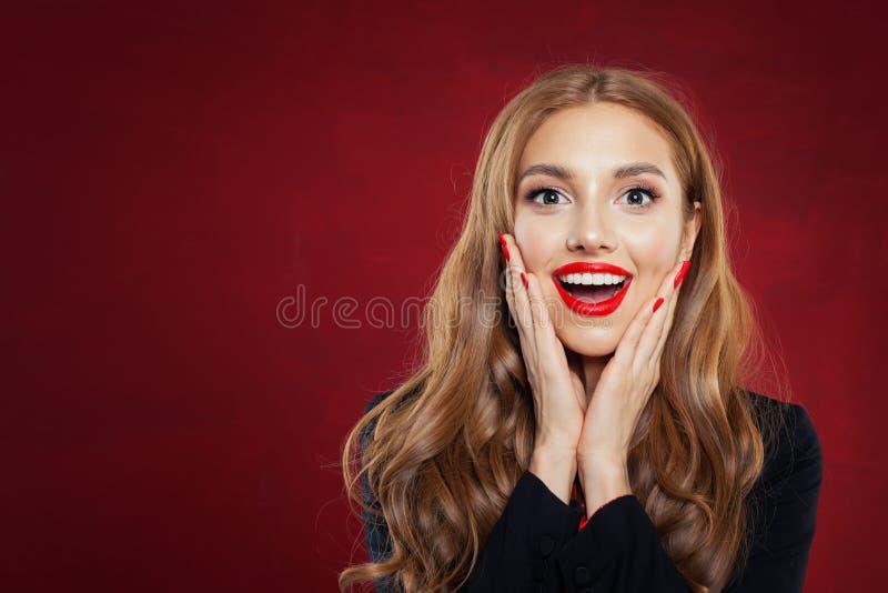 Jonge gelukkige vrouw tegen rode muurachtergrond Verrast meisjesportret Positieve emoties, gelaatsuitdrukking royalty-vrije stock afbeeldingen