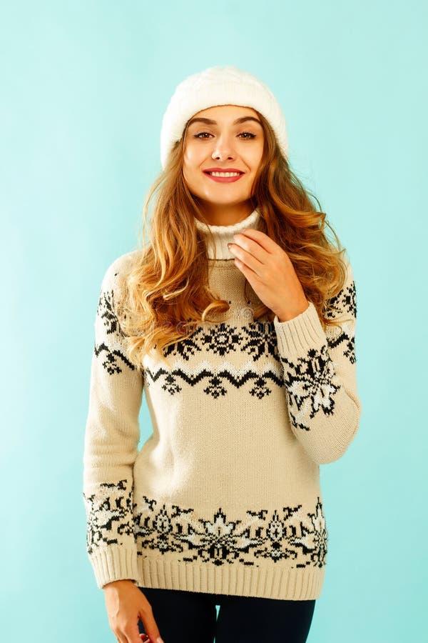 Jonge gelukkige vrouw in warme sweater over blauwe achtergrond royalty-vrije stock fotografie