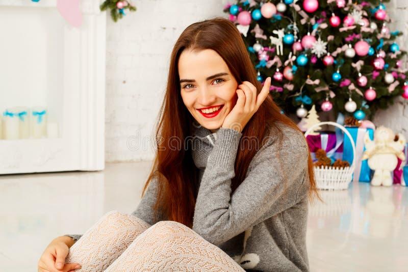 Jonge gelukkige vrouw in warme sweather dichtbij nieuwe jaarboom met pres stock fotografie