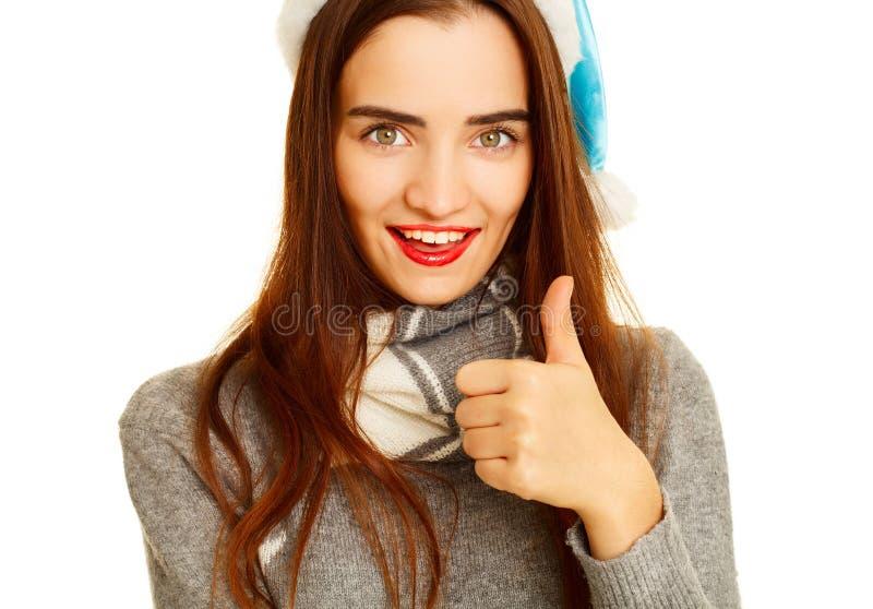 Jonge gelukkige vrouw in warme sweather die hand o.k. teken over wh tonen stock fotografie
