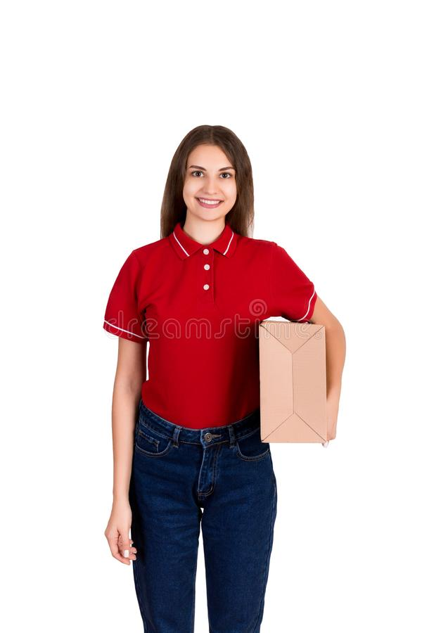Jonge gelukkige vrouwelijke levering met een pakket in haar die handen op witte achtergrond wordt geïsoleerd stock fotografie