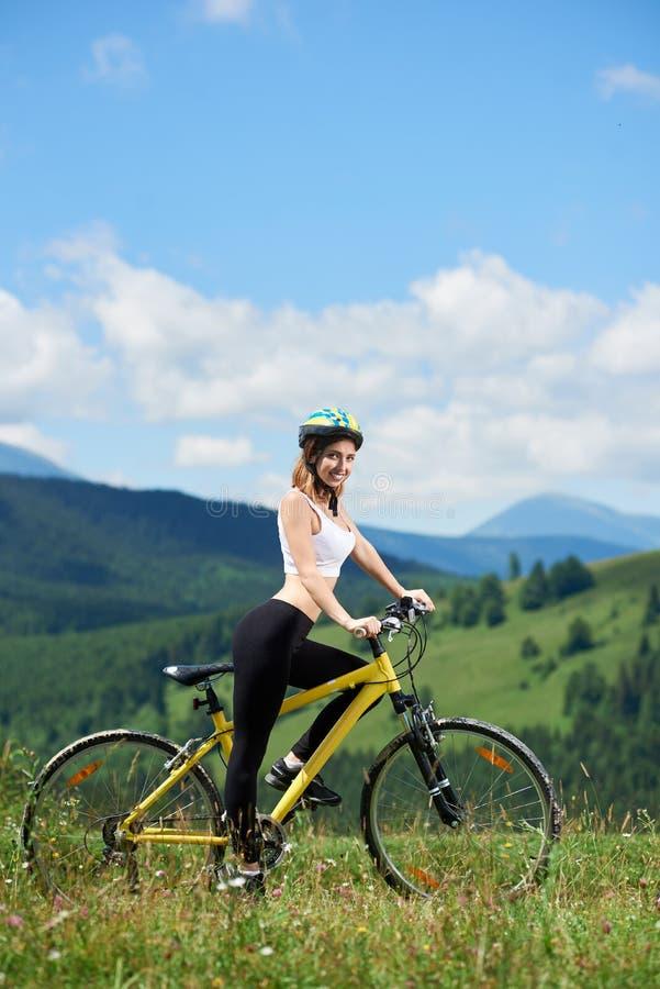 Jonge gelukkige vrouwen berijdende fiets in de bergen bij de zomerdag royalty-vrije stock foto's