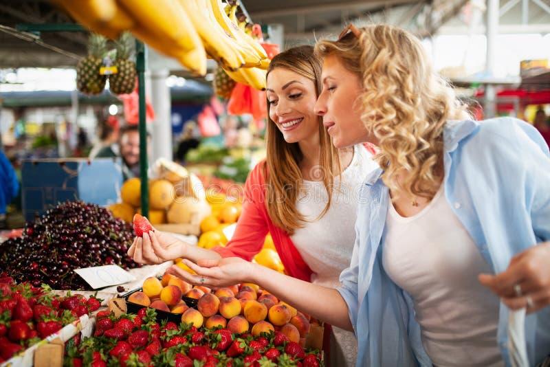 Jonge gelukkige vrouwen het winkelen groenten en vruchten op de markt royalty-vrije stock afbeelding