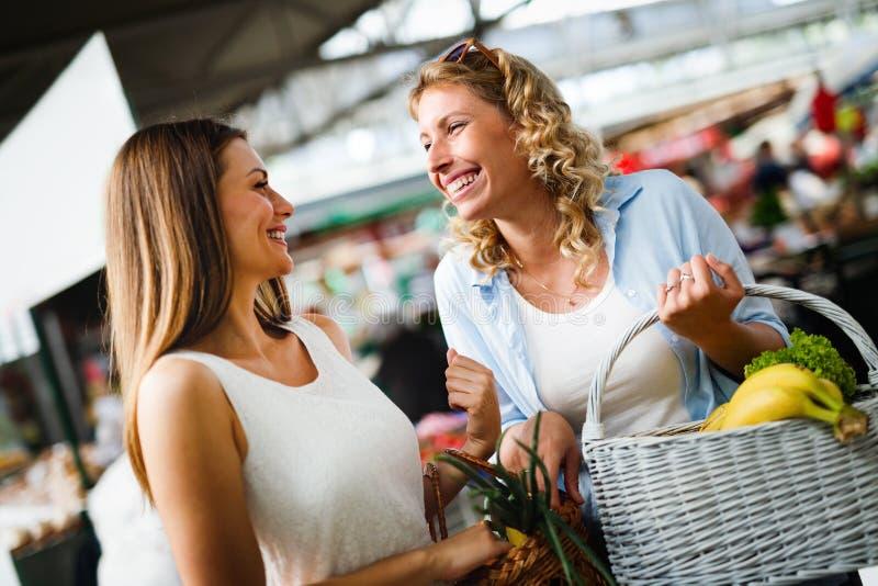 Jonge gelukkige vrouwen het winkelen groenten en vruchten op de markt royalty-vrije stock fotografie