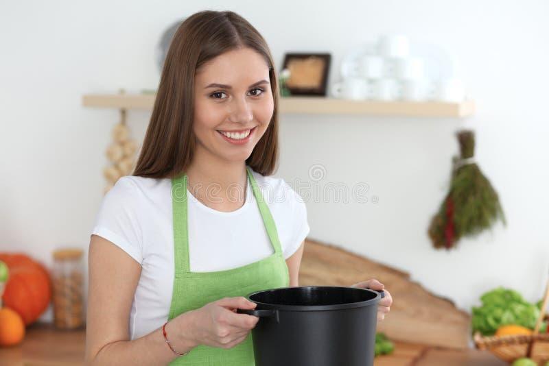 Jonge gelukkige vrouwen kokende soep in de keuken Gezonde maaltijd, levensstijl en culinair concept Glimlachend studentenmeisje royalty-vrije stock afbeelding