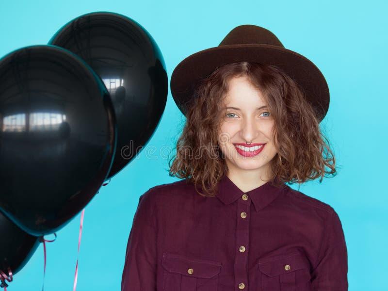 Jonge gelukkige vrouwenkunstenaar met zwarte ballons die naar verjaardag gaan stock afbeelding