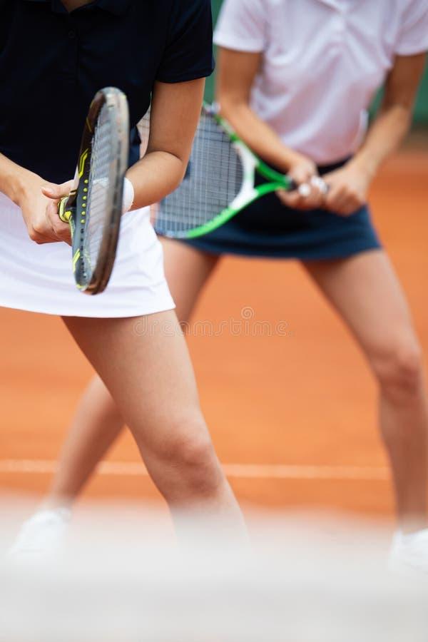Jonge gelukkige vrouwenvrienden die tennis spelen bij tennisbaan royalty-vrije stock foto