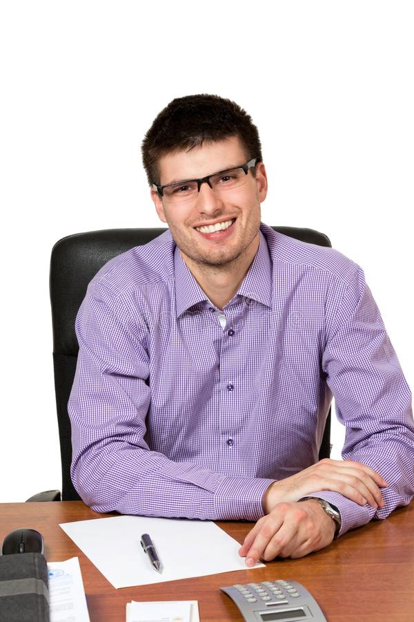 Jonge gelukkige zakenman die bij zijn bureau werken royalty-vrije stock fotografie