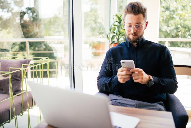 Jonge gelukkige zakenman het glimlachen zitting in bureau met laptop terwijl het lezen van zijn smartphone Portret van het glimla royalty-vrije stock afbeelding