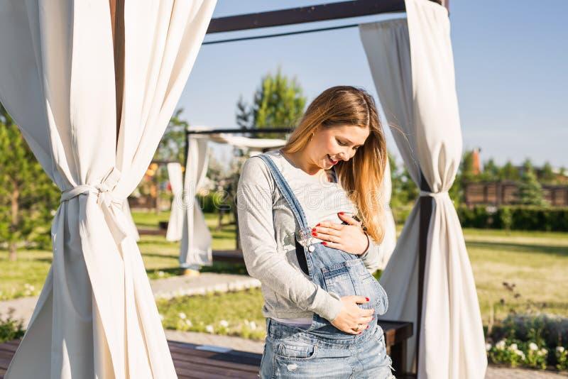 Jonge gelukkige zwangere vrouw die en van het leven in de herfstaard ontspannen genieten royalty-vrije stock foto's