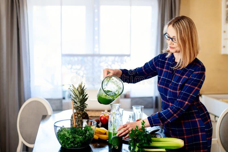 Jonge gelukkige zwangere vrouw die groene smoothie gieten aan glaskop royalty-vrije stock foto