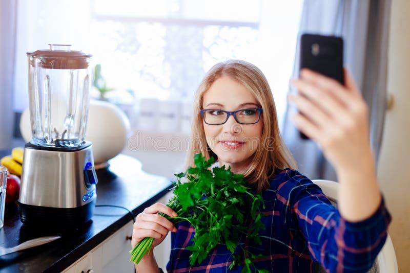 Jonge gelukkige zwangere vrouw die selfie foto met telefoon met groene peterselie nemen royalty-vrije stock afbeelding