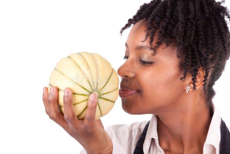 Jonge gelukkige zwarte/Afrikaanse Amerikaanse vrouw die een verse melo ruiken stock foto