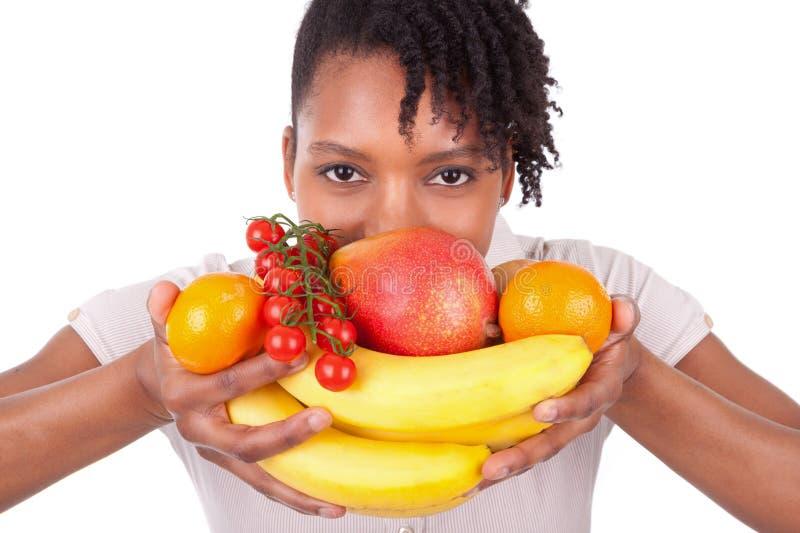 Jonge gelukkige zwarte/Afrikaanse Amerikaanse vrouw die verse vruchten houdt royalty-vrije stock foto