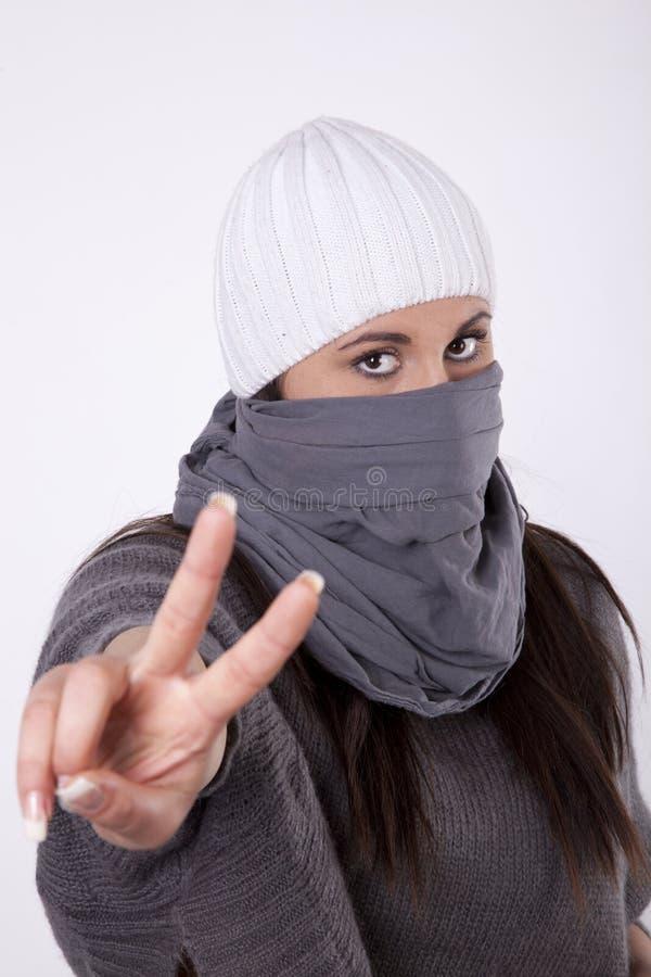 Jonge gemaskeerde vrouw met het tonen van vredesteken stock fotografie