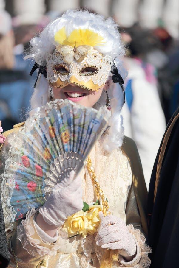 Jonge gemaskeerde vrouw met ventilator in Carnaval van Venetië stock foto's