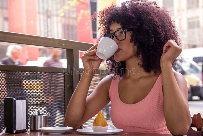 Jonge gemengde vrouw met zitting die van het afrokapsel de in openlucht drinken royalty-vrije stock foto's