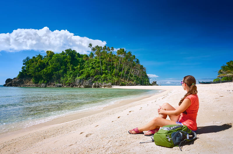 Jonge gerl met rugzak het ontspannen op kust en het kijken aan een isla stock afbeelding