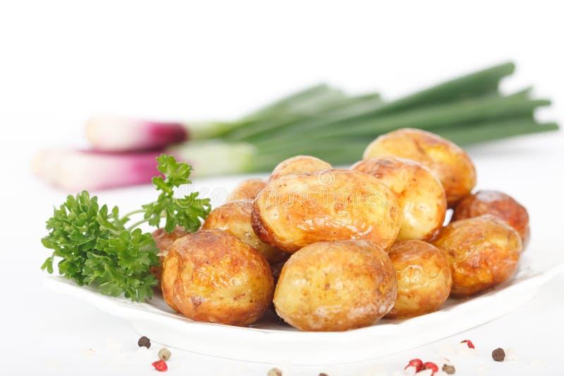 Jonge geroosterde aardappels met peterselie en de lenteuien royalty-vrije stock foto