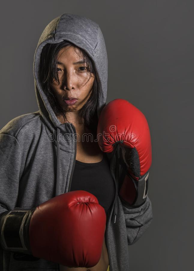 Jonge geschikte en gezonde Aziatische Koreaanse bokservrouw in geschiktheidsbovenkant hoodie en bokshandschoenen die koele badass royalty-vrije stock afbeeldingen