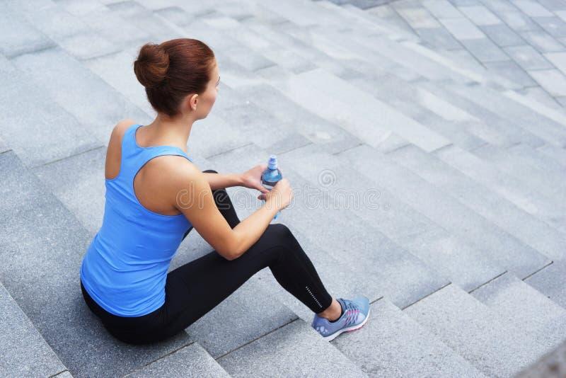 Jonge, geschikte en sportieve vrouw die na de opleiding rusten Fitness, sport, stedelijke jogging, gezond levensstijlconcept stock afbeelding