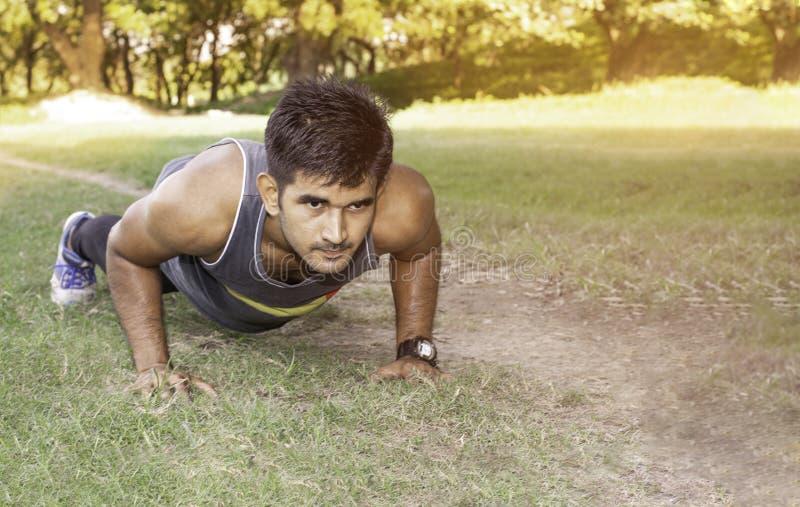 Jonge geschikte Kaukasische mens die opdrukoefeningen in openlucht op zonnige de zomerdag doen Fitness en het concept van de spor royalty-vrije stock foto's
