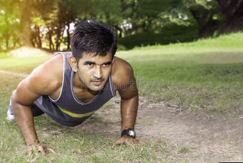 Jonge geschikte Kaukasische mens die opdrukoefeningen in openlucht op zonnige de zomerdag doen Fitness en het concept van de spor stock afbeelding