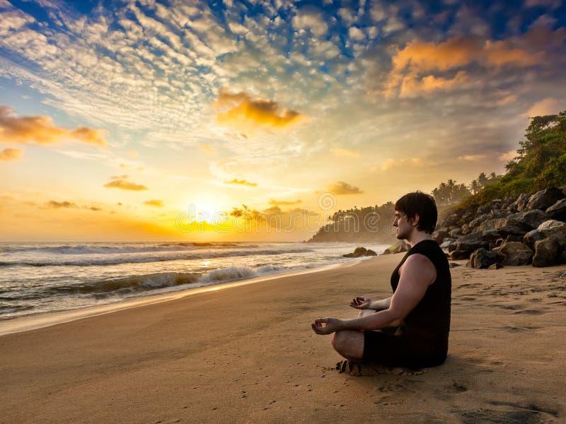 Jonge geschikte man do yoga meditatie op tropisch strand royalty-vrije stock fotografie