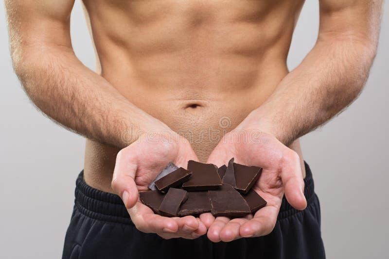 Jonge geschikte mens die donkere chocoladestukken houden stock fotografie