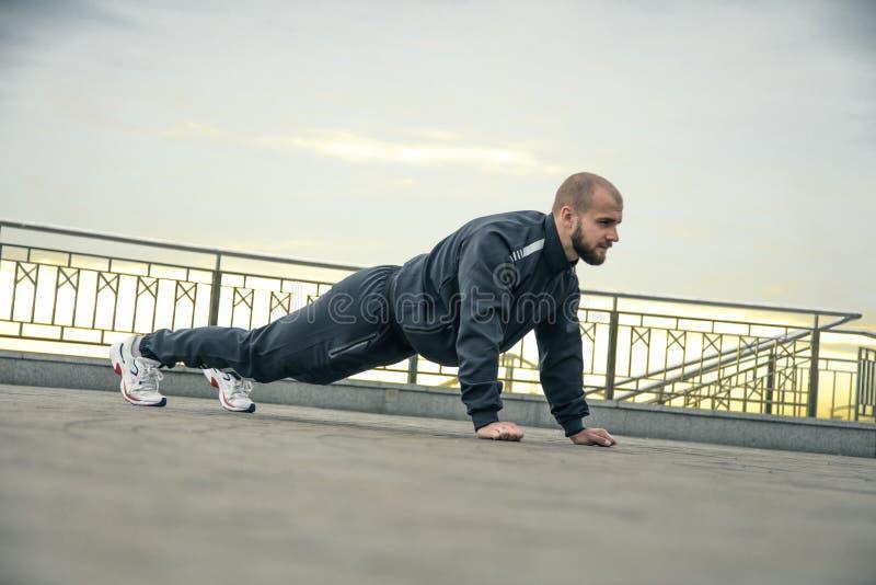 Jonge geschikte shirtless Kaukasische mens die opdrukoefeningen in openlucht op zonnige de zomerdag doen Fitness en het concept v royalty-vrije stock foto