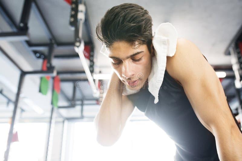 Jonge geschikte Spaanse mens in gymnastiek afvegend zweet van zijn gezicht royalty-vrije stock foto's