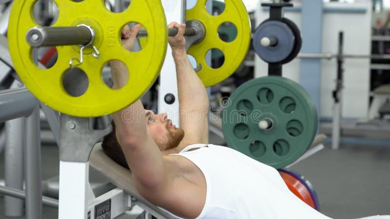 Jonge geschikte sportman die barbell bank doen die terwijl het uitoefenen bij geschiktheidsclub drukken Spiermens die in de Gymna stock fotografie