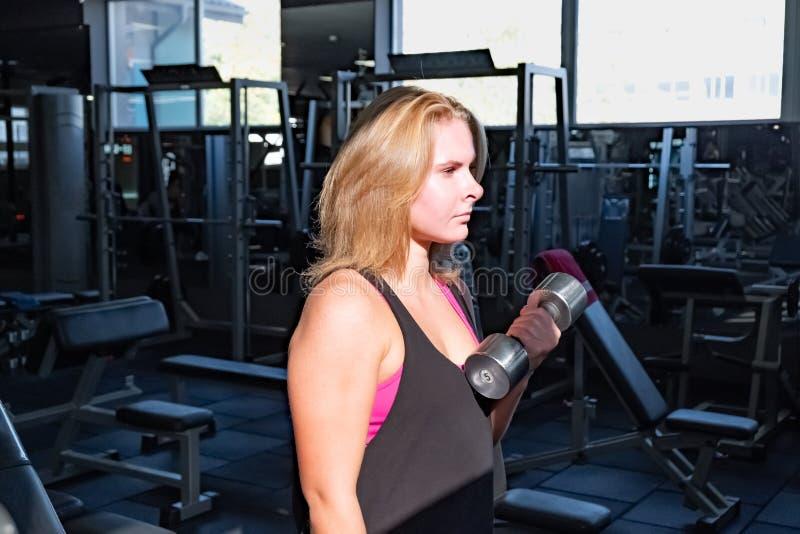 Jonge geschikte vrouw bij de gymnastiek die heavylifting oefening met bar doen royalty-vrije stock foto