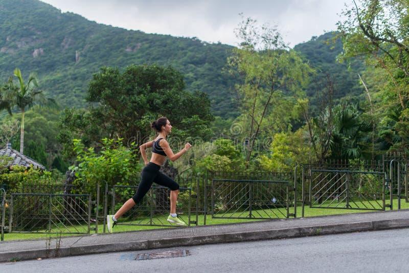 Jonge geschikte vrouw die cardiooefening doen, luisterend aan muziek, die in openlucht met groen berglandschap lopen in stock fotografie