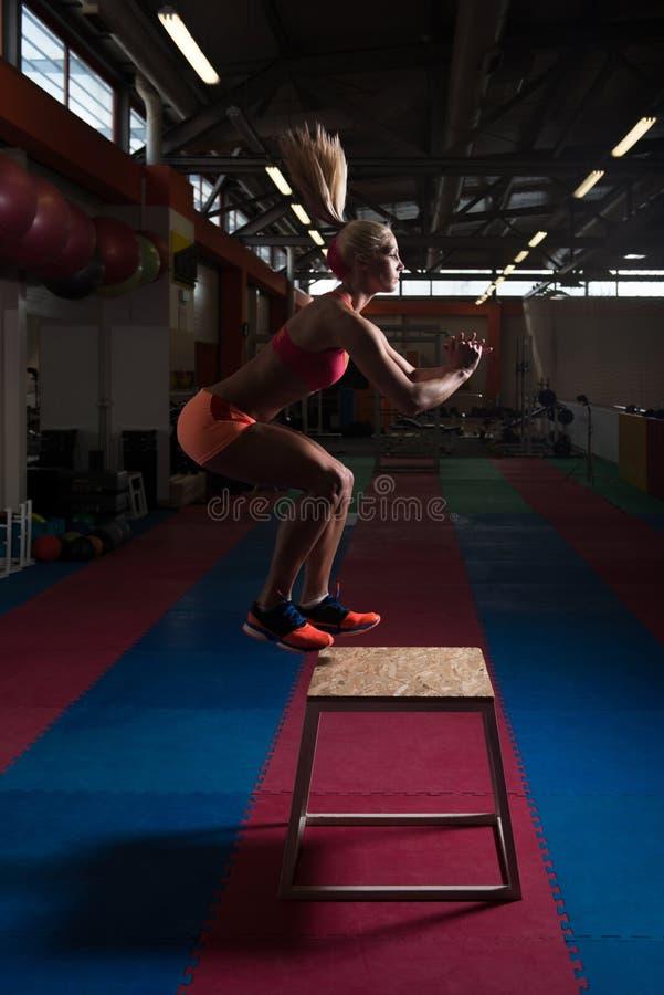 Jonge Geschikte Vrouw die Doossprongen in Gymnastiek doen stock fotografie