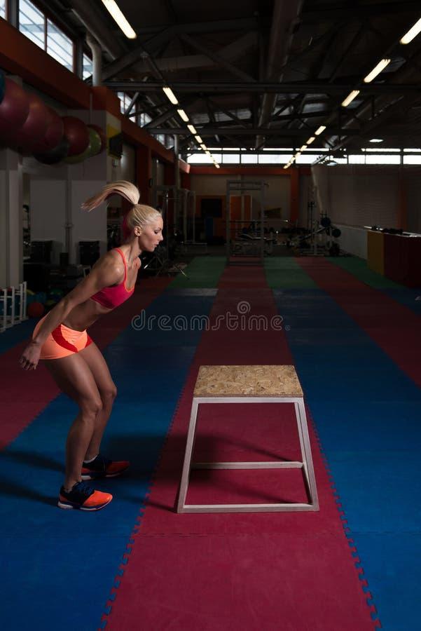 Jonge Geschikte Vrouw die Doossprongen in Gymnastiek doen stock afbeeldingen