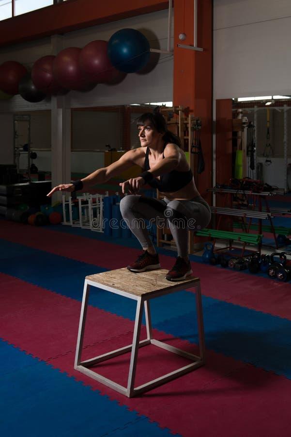Jonge Geschikte Vrouw die Doossprongen in Gymnastiek doen royalty-vrije stock afbeelding