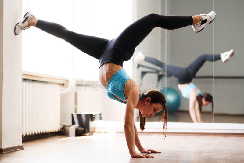 Jonge geschikte vrouw die handstandoefening in gymnastiek doen royalty-vrije stock afbeelding
