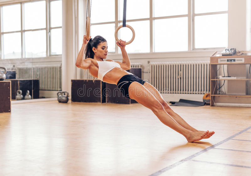 Jonge geschikte vrouw die trekkracht-UPS op gymnastiek- ringen doen royalty-vrije stock foto