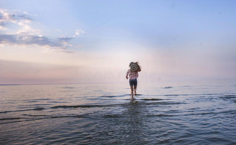 Jonge geschikte vrouwenjogging bij een strand in bikini in Bali Openlucht lopen of het uitwerken Geschikte vrouw die bij leeg oce stock foto