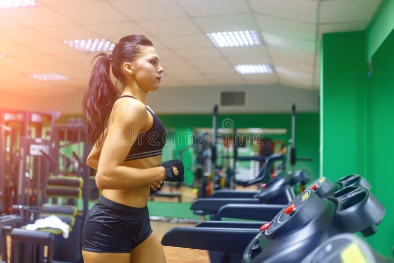 Jonge geschiktheidsvrouw die cardiooefeningen doen bij de gymnastiek die op een tredmolen vrouwelijke agent lopen die bij gim opl royalty-vrije stock foto