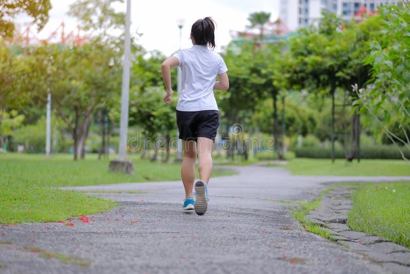 jonge geschiktheidsvrouw die in de park openlucht, vrouwelijke agent op de weg buiten lopen, Aziatische atletenjogging en oefenin royalty-vrije stock fotografie