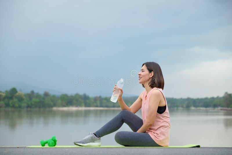 Jonge Geschiktheidsvrouw die en drinkwater na yoga in het park glimlachen houden Gezond levensstijlconcept stock afbeelding