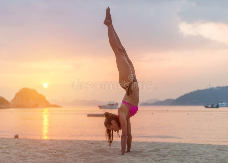 Jonge geschiktheidsvrouw die handstandoefening op strand doen bij zonsopgang Sportief meisje in bikini het praktizeren yogakust stock afbeelding
