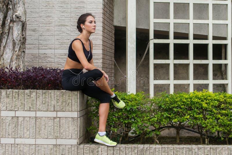Jonge geschiktheidsvrouw die rust na het lopen in stad hebben Vermoeid sportief meisje die en aan muziek in hoofdtelefoons zitten stock afbeelding