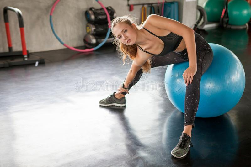 jonge geschiktheidsvrouw in sportkleding die haar benen op blauwe bal uitrekken vóór Oefening in gymnastiek sport geschikte meisj stock foto