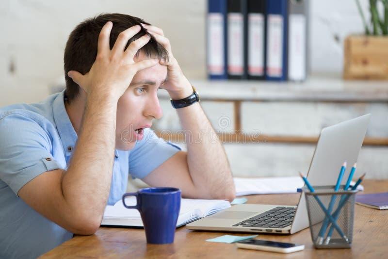 Jonge geschokte bureaumens die laptop computer bekijken royalty-vrije stock afbeelding