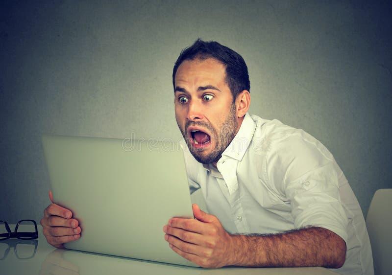 Jonge geschokte mens met laptop computerzitting bij lijst royalty-vrije stock foto